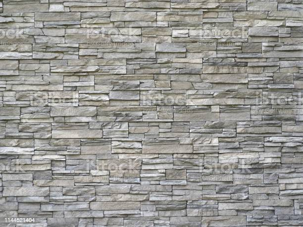 Photo of Stone cladding wall made of  striped stacked slabs of natural gray rocks. Panels for exterior.