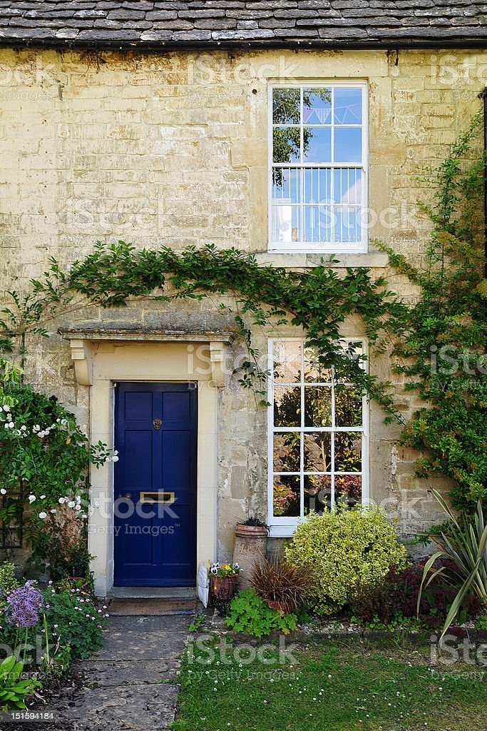 Stone cottage with Windows and blue door stock photo