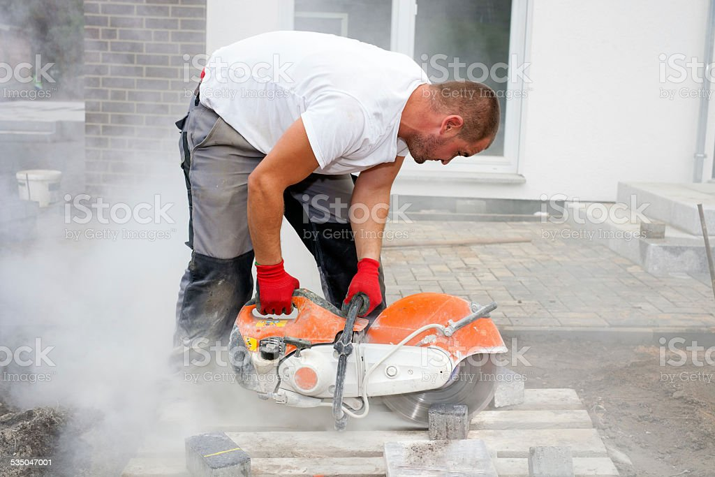 Stone cutter at work on construction site. stock photo