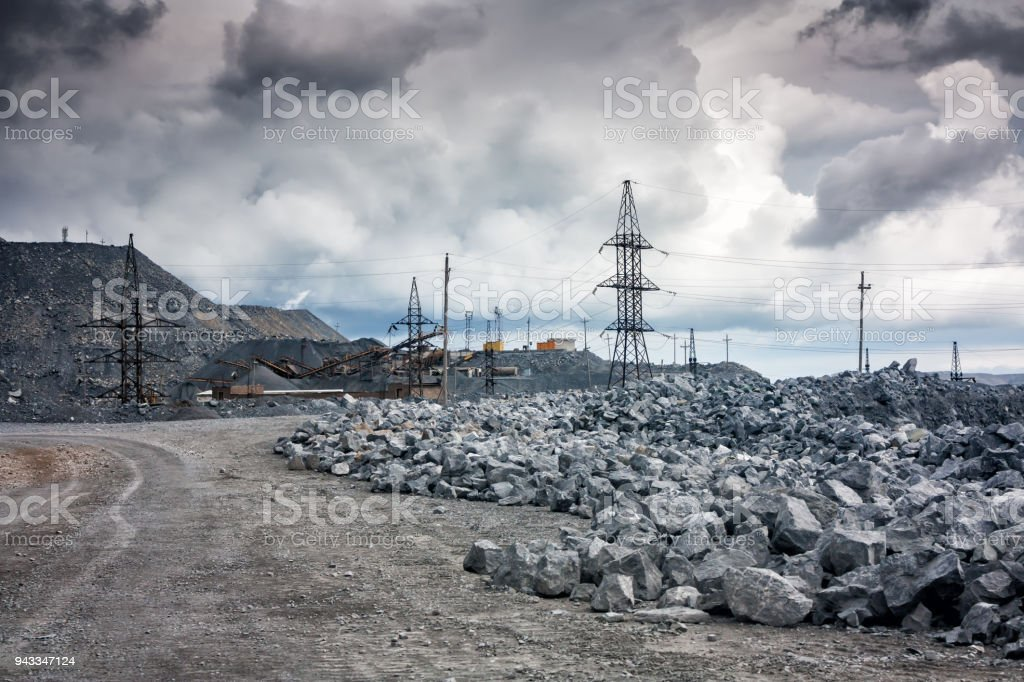 Stone dumps, power lines and crushing machines in a quarry in cloudy weather стоковое фото