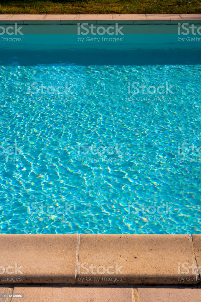 Stone edging detail beside a blue swimming pool sunshine surface ripples. stock photo