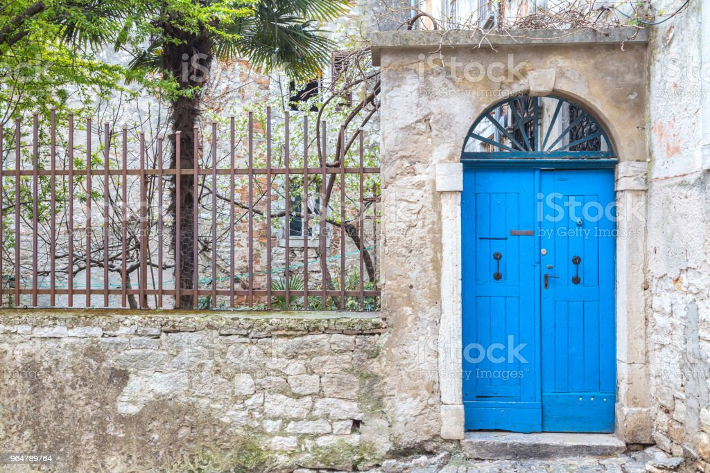 Stone facade with a blue entrance door of an old house in Rovinj royalty-free stock photo