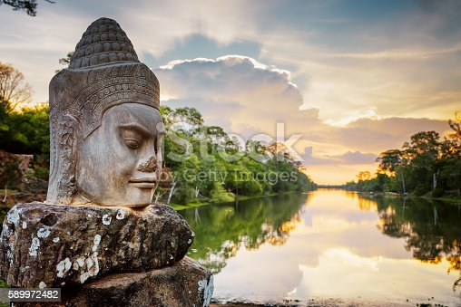 Stone face Asura on causeway near South Gate of Angkor Thom in Siem Reap, Cambodia. Beautiful sunset over ancient moat in background. Mysterious Angkor Thom is a popular tourist attraction.