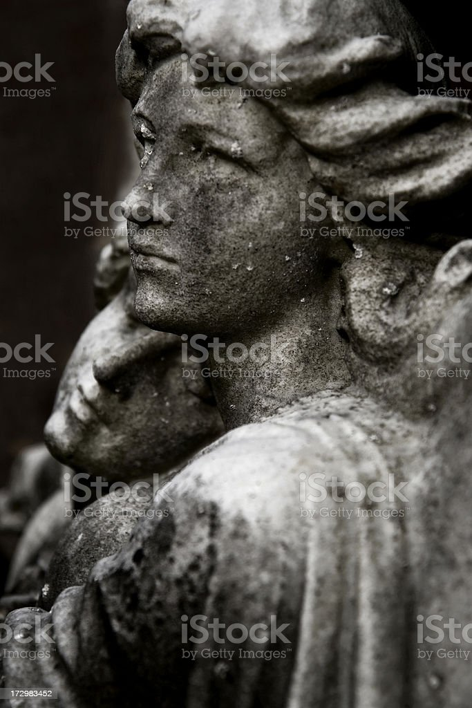 Stone figures embracing on tomb stock photo