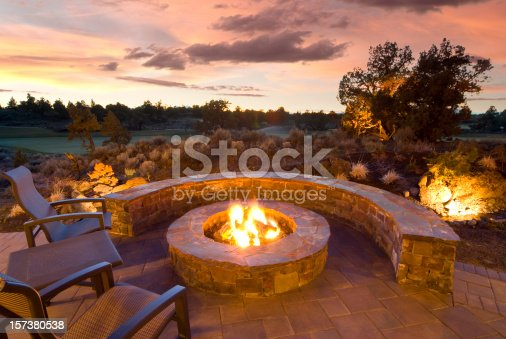 stone fire pit with outdoor chairs, enjoying the sunset and landscape.