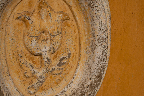 Stone flower carving on stucco wall