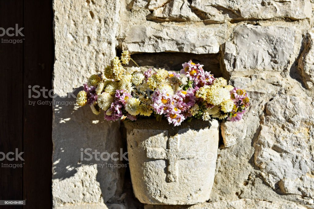 Stone Flower Vase At The Wall Of The Old Church Stock Photo & More on bridesmaid bouquets for vases, church sanctuary flowers, plants for vases, church flowers large, church flower decorations, church flowers for christmas, church wedding flowers, church pew decorations for weddings, flower arrangements for vases, jelly beads for vases,