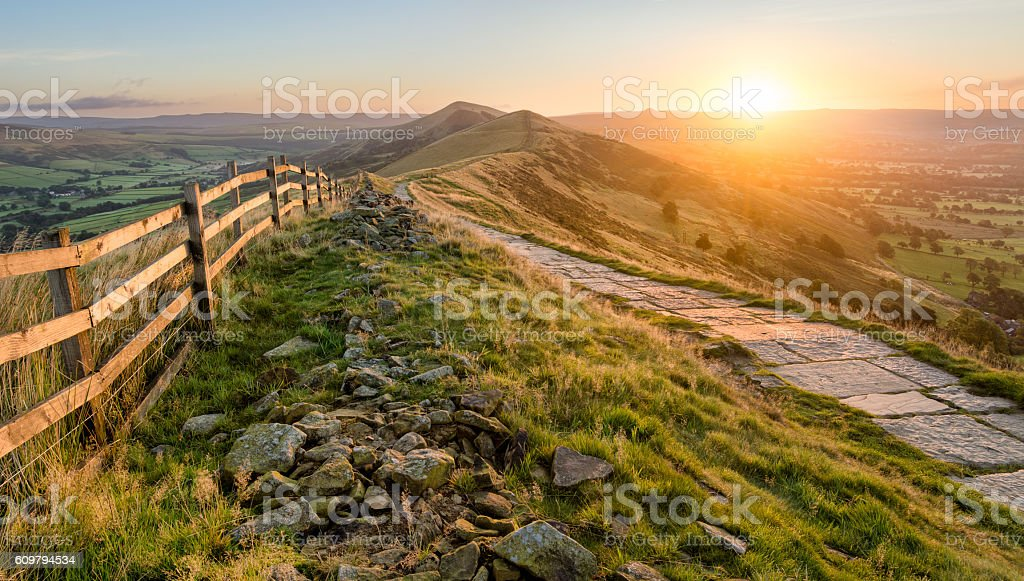 Stone Footpath Along Mountain Ridge In Peak District. A stone footpath and wooden fence leading a long The Great Ridge in the English Peak District. Taken at sunrise, the image features beautiful Autumn vibrant colours from the rising sun. Adventure Stock Photo
