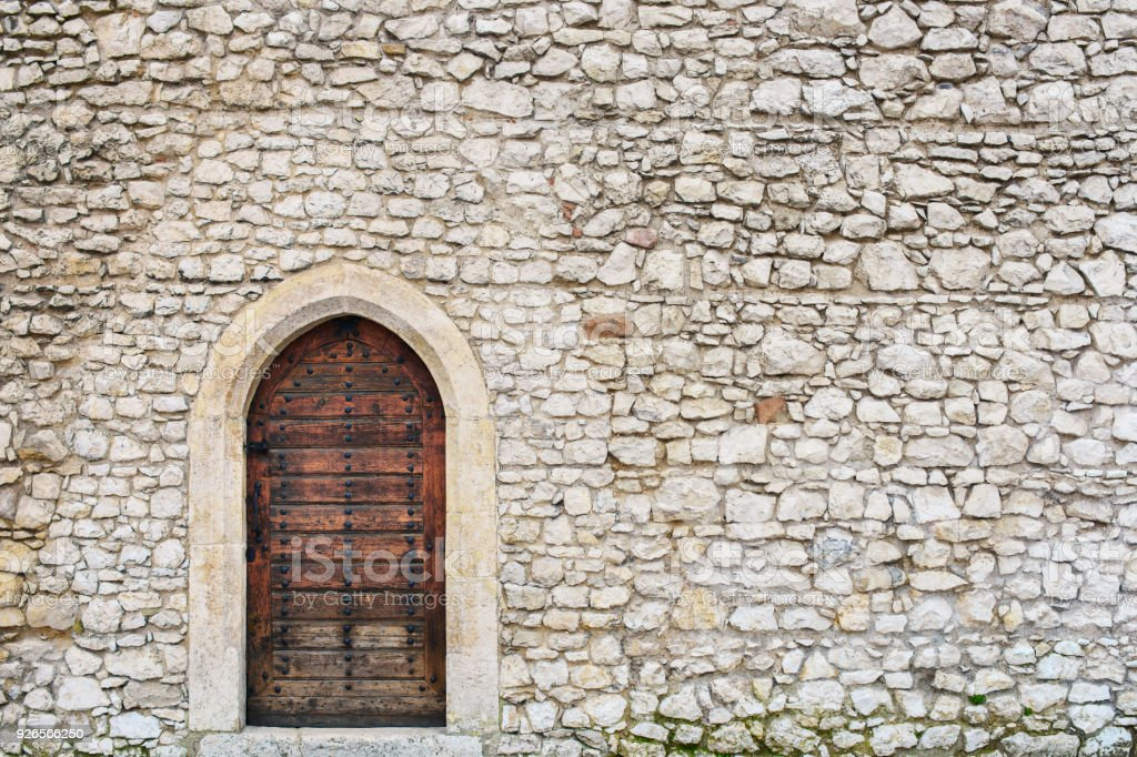 Stone fortress castle wall of a medieval castle, an old wooden closed arcade door with iron rivets. Place for text, copuspace