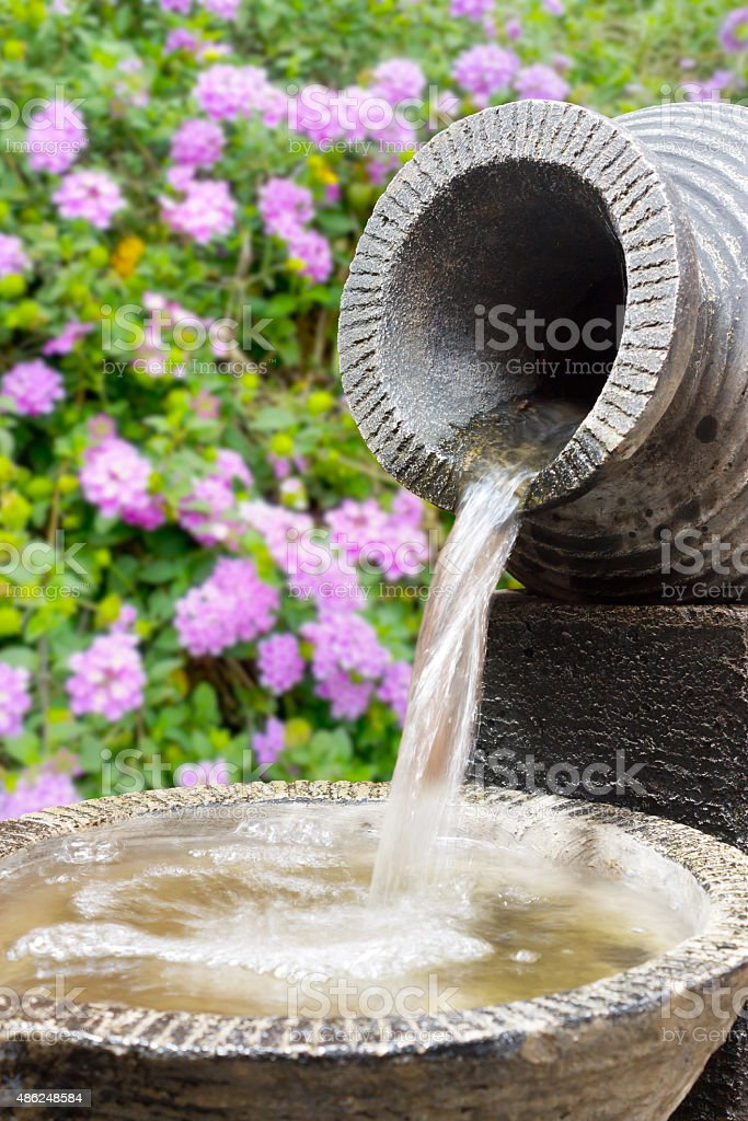 Stone Fountain With Flowers On The Background stock photo