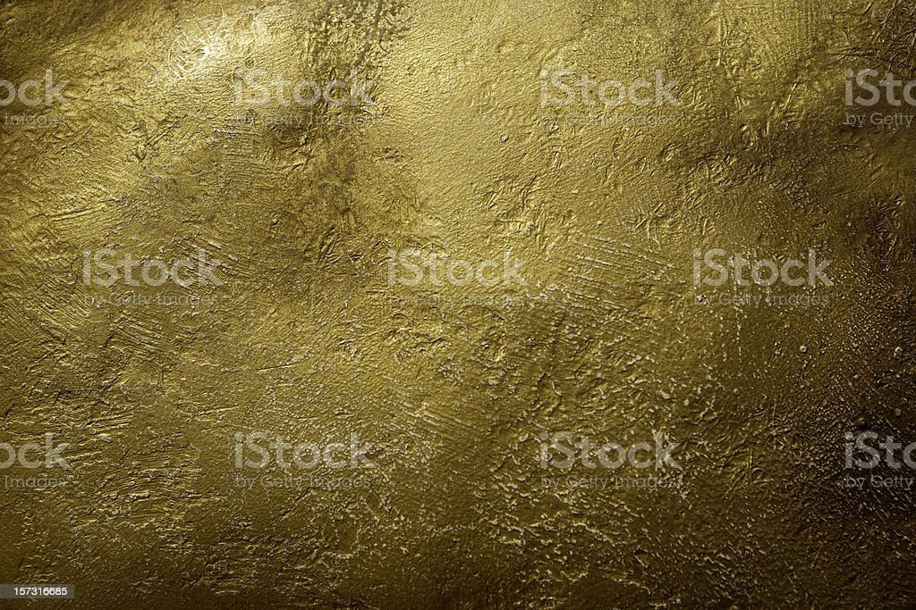 Stone gold wall under a faint source of light stock photo