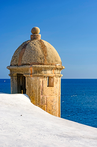 Stone guardhouse on the walls of an old colonial-style fort with the blue sea in background on the seafront of Salvador in Bahia
