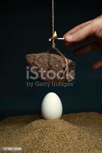 Stone hanging on a rope over the egg which stands on the sand