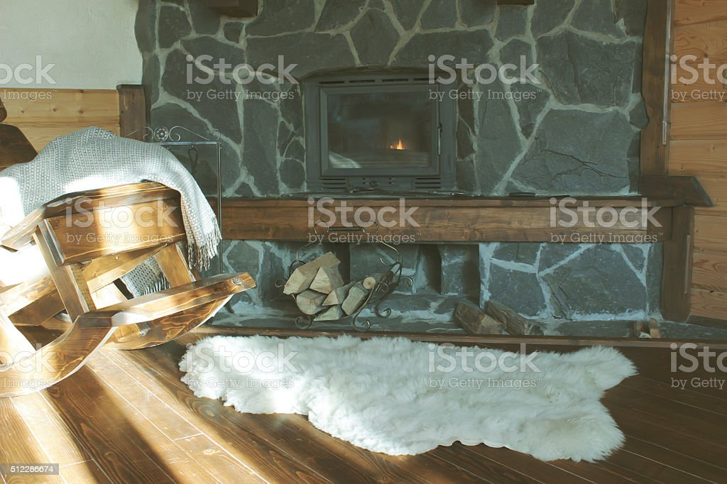 Stone hearth fireplace with wooden rocking chair stock photo