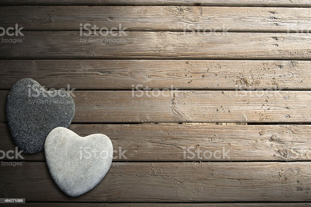 Stone Hearts on Wooden Boardwalk with Sand stock photo