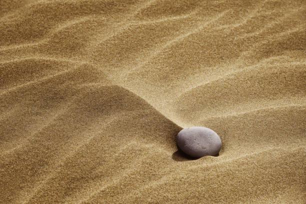 Stone in desert sand. stock photo
