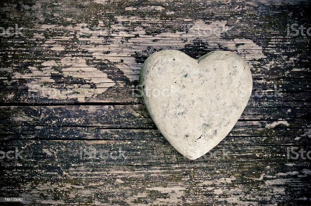 A stone in the shape of a heart on a wooden surface stock photo