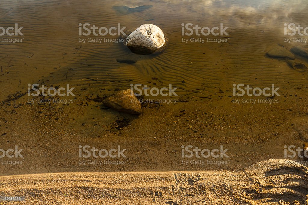 Stone in water on shore of lake royalty-free stock photo