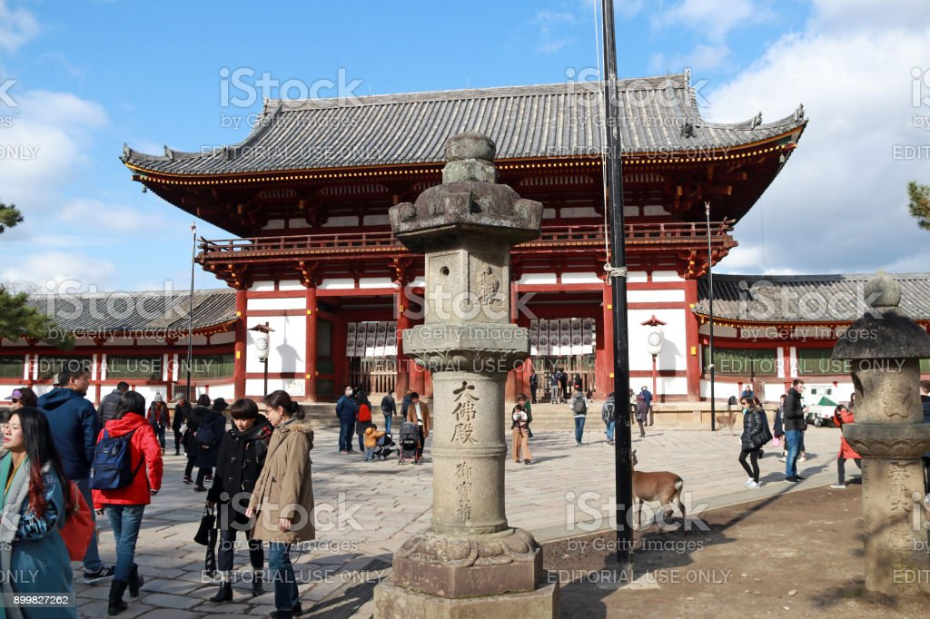 Stone lantern in front of the second antique wooden archway entrance of Todaiji temple and many tourist with green tree on blue sky background. stock photo