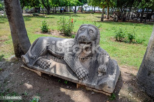 Stone lion carved from a piece of limestone. Statue in the park.