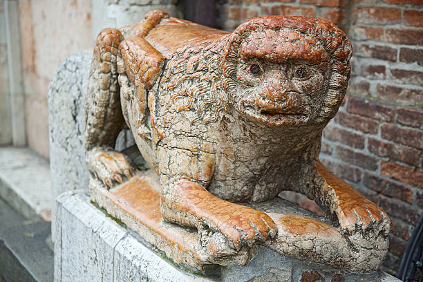 stone lion statue in front of ferrara cathedral entrance - demoniac stock pictures, royalty-free photos & images