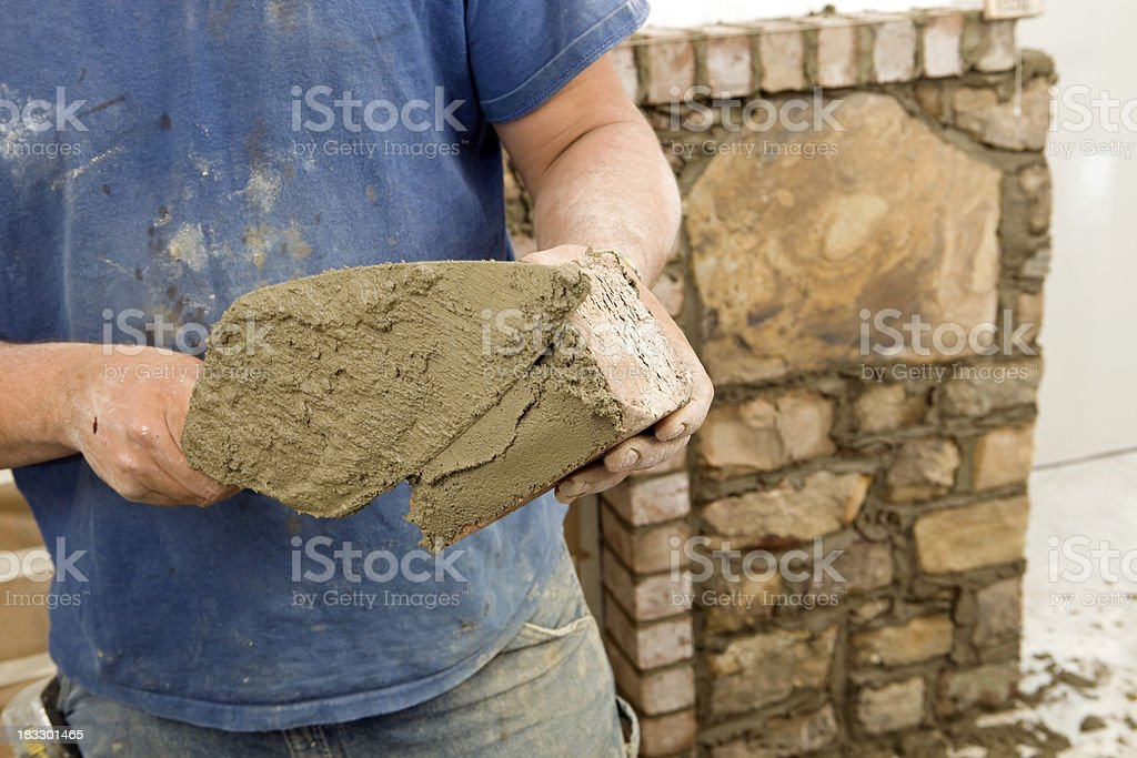 Stone Mason Buttering  Brick with Mortar for New Fireplace Surround royalty-free stock photo