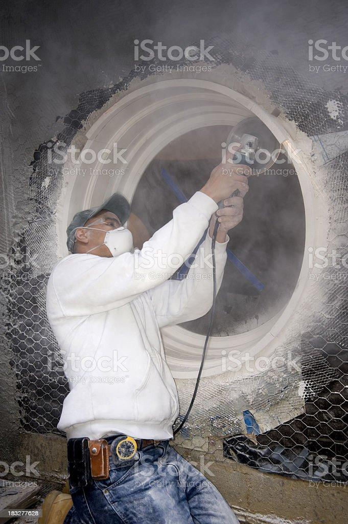 stone mason using a grinder stock photo