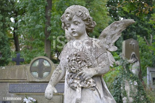 istock Stone monument statue in the shape of an angel with flowers 1135959369