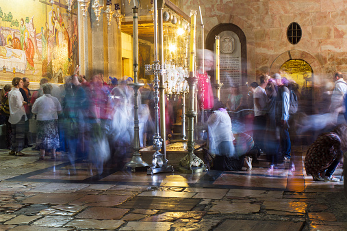 Jerusalem , Israel - November 02 . 2014 : The pilgrims passionately prays under icon lamps in the church of the Holy Sepulcher . This oldest Christian sanctuary - Stone of Unction