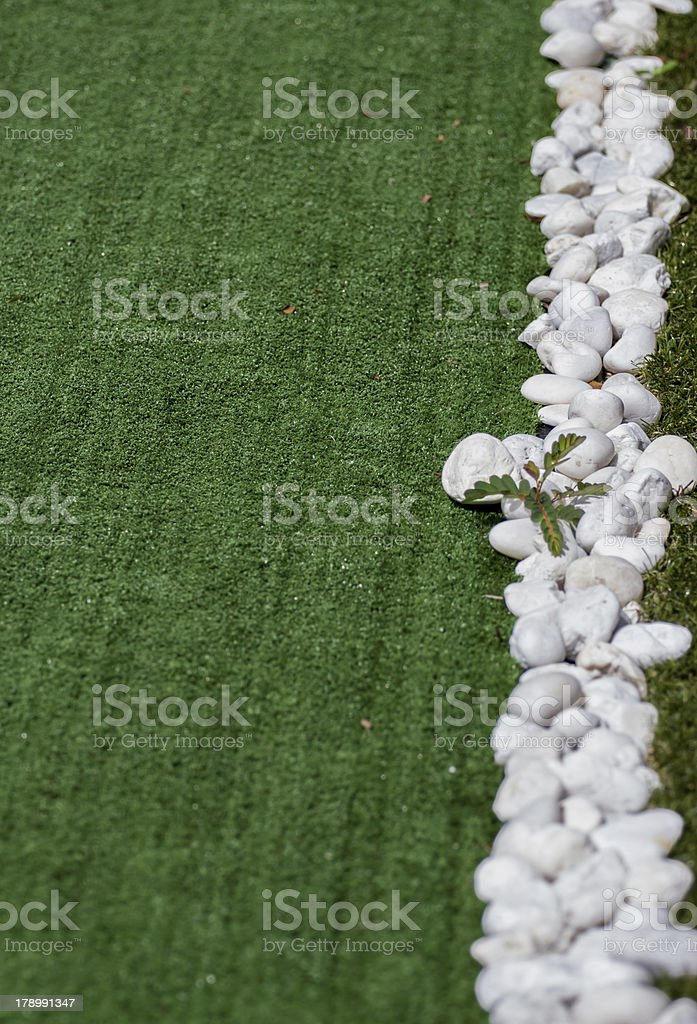 Stone on artificial rolled green grass royalty-free stock photo