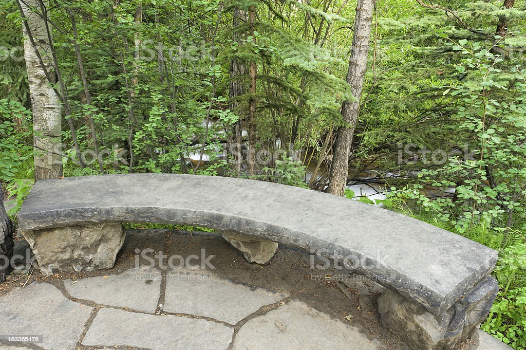 Stone Park Bench in Zen Garden Along Mountain Stream stock photo