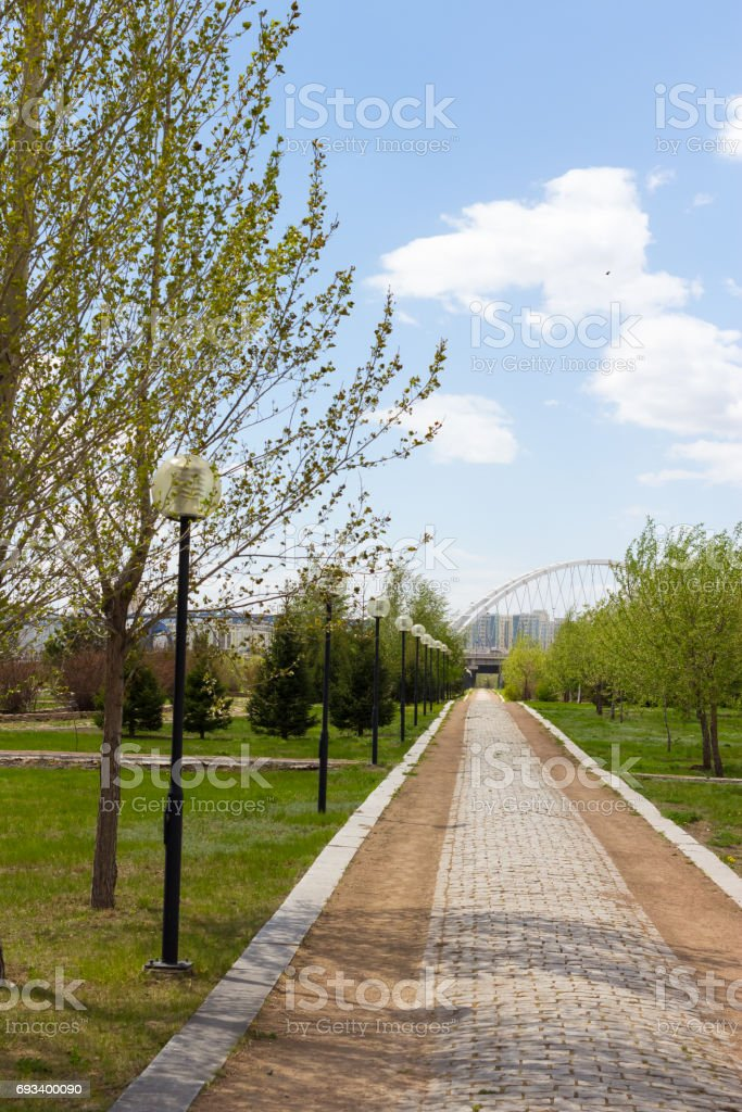 Stone path leading to the bridge in the Park of Astana. Sunny day stock photo