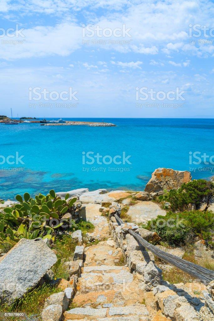 Stone path to beautiful Spiaggia del Riso beach with azure sea water, Sardinia island, Italy stock photo