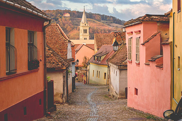 stone paved old streets with colorful houses in sighisoara - romania stock photos and pictures
