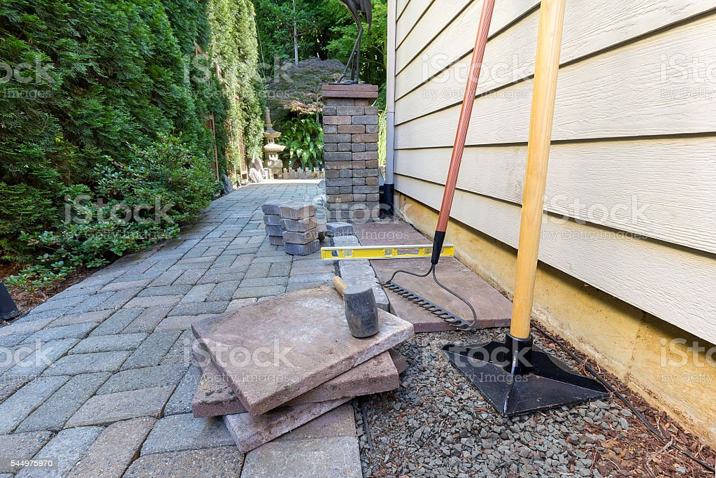 Stone Pavers and Tools for Side Yard House Landscaping stock photo