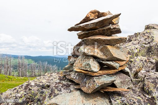 Close-up of stones that fell from a cliff, made up of a pyramid stand against the backdrop of mountains and forests. The texture of gray stone, the background.