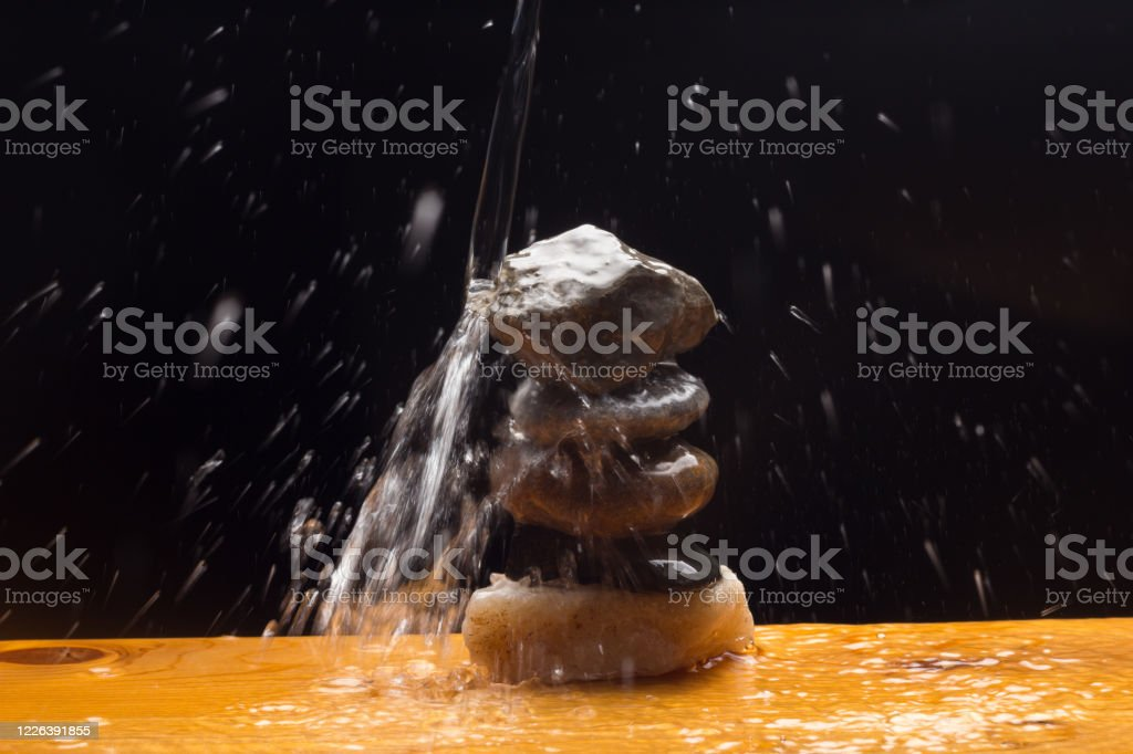 stone Crystal clear, drinkable and transparent water, falling on some stones and creating thousands of drops due to splashing and splashing water. Abundance Stock Photo