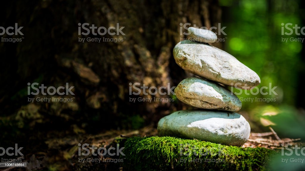 stone pyramid on moss in the forest stock photo