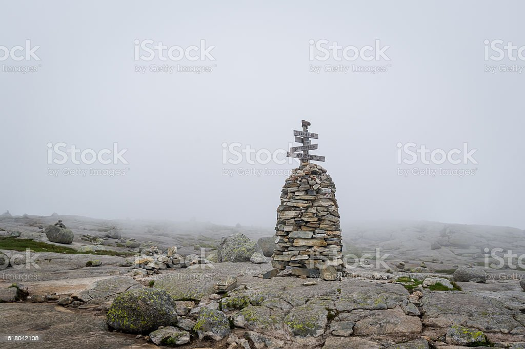 Stone pyramide with hiking path route sign in the foggy stock photo