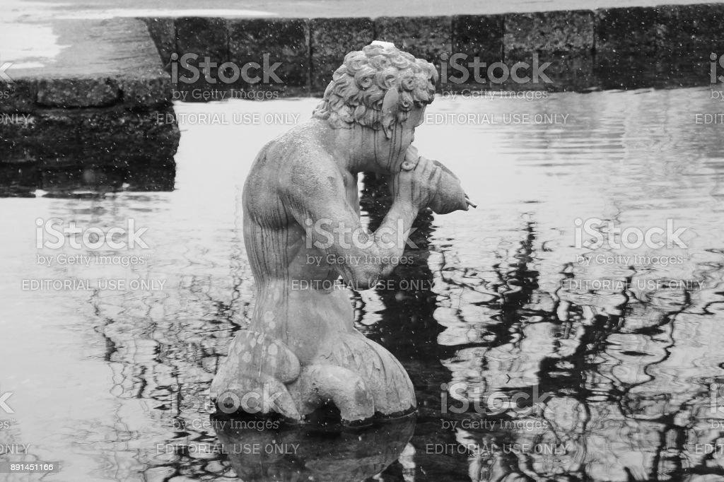 Stone sculpture of a Triton, in the public garden of Hellbrunn. Salzburg, Austria. stock photo