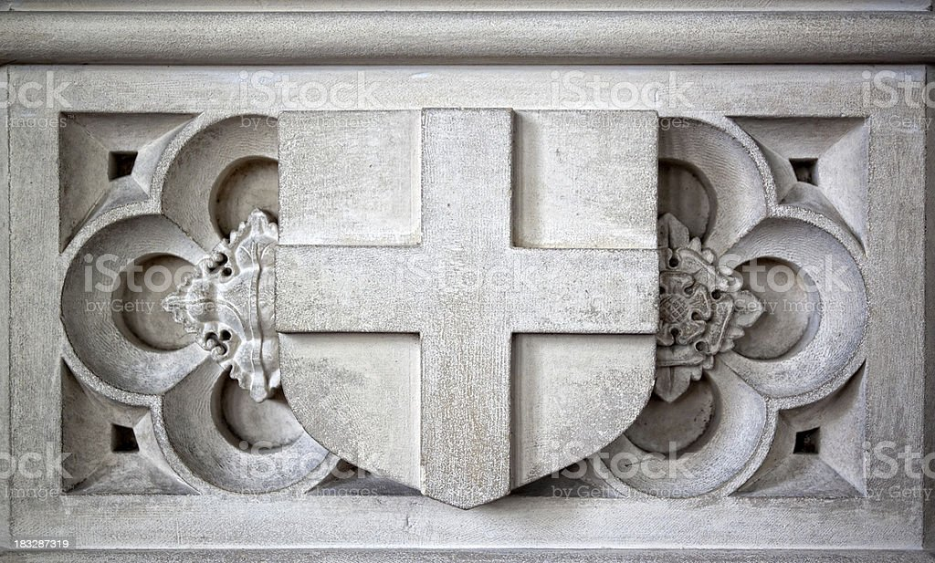 Stone shield and cross detail on a church font stock photo