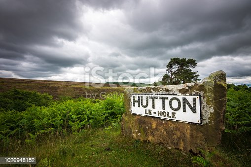 A beautiful rural North Yorkshire scene serves as a backdrop for the sign. The overcast sky adds to the dramatic English scene.