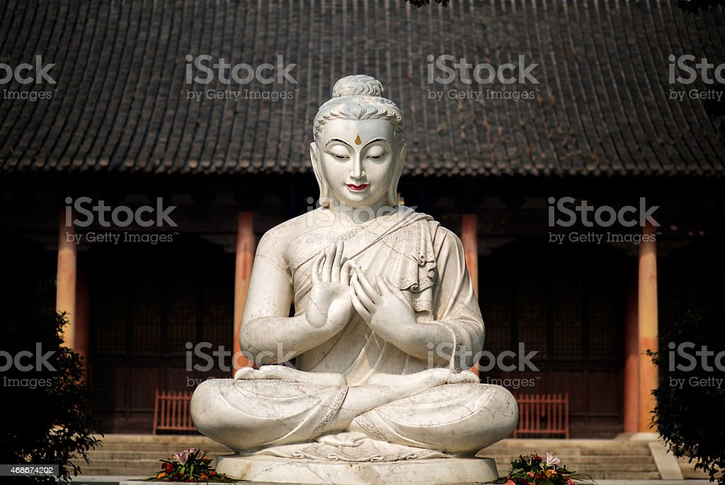 stone sitting Buddha statue in an ancient temple stock photo