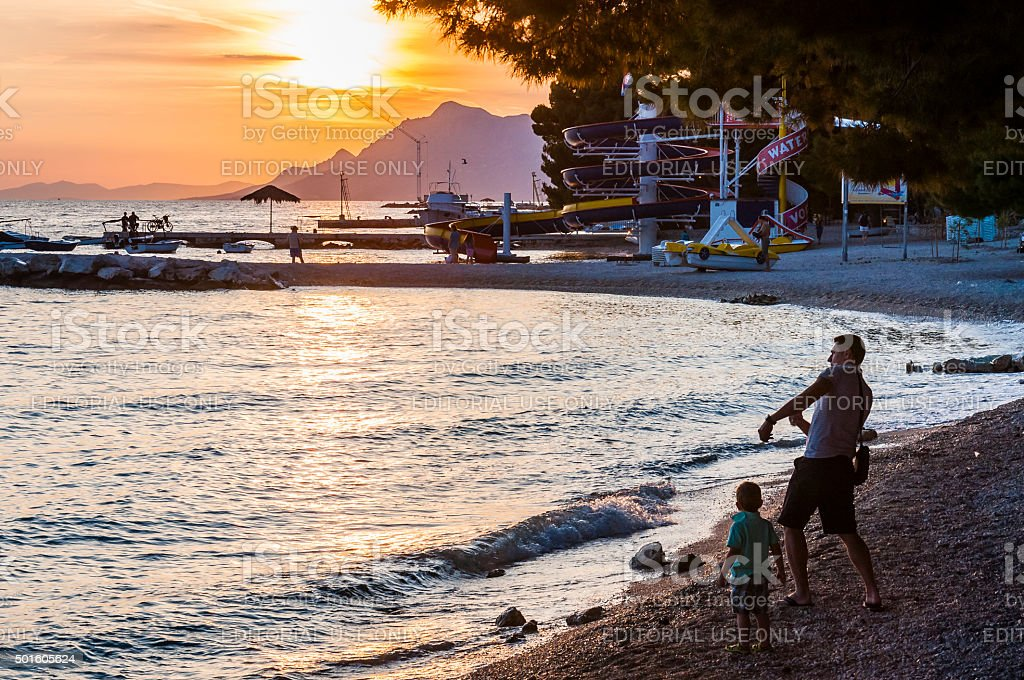 Stone skipping lesson. Father with sun on the beach. Sunset. stock photo