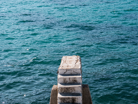 Old lonely stone stairway on concrete sea breakwater top view