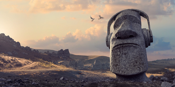 A single large Moai style stone head statue wearing headphones as if listening to music, formed from solid rock, buried in the ground from the neck down. The statue is located in a generic remote rocky landscape at dawn, as two birds fly towards it. With copy space.