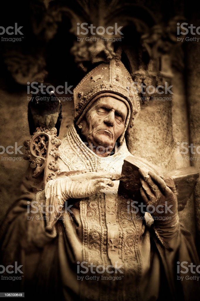 Stone Statue of Bishop with Pigeon Sitting on Shoulder royalty-free stock photo