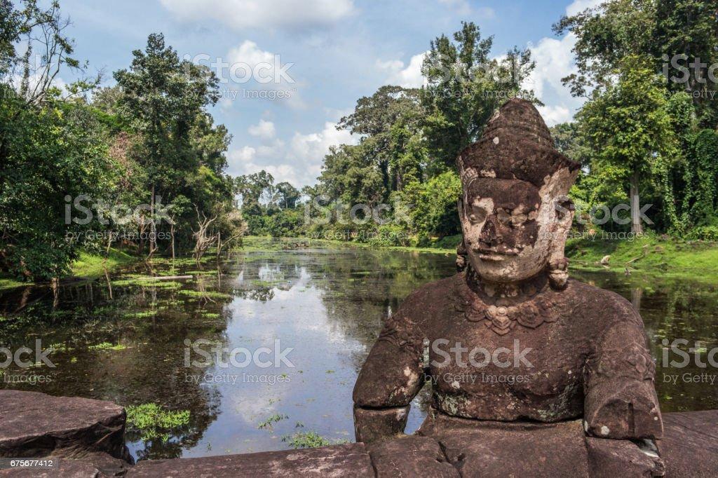 Statue en pierre de gardien Asura sur le pont qui enjambe les douves entourant le temple de Preah Khan, Angkor, Cambodge photo libre de droits