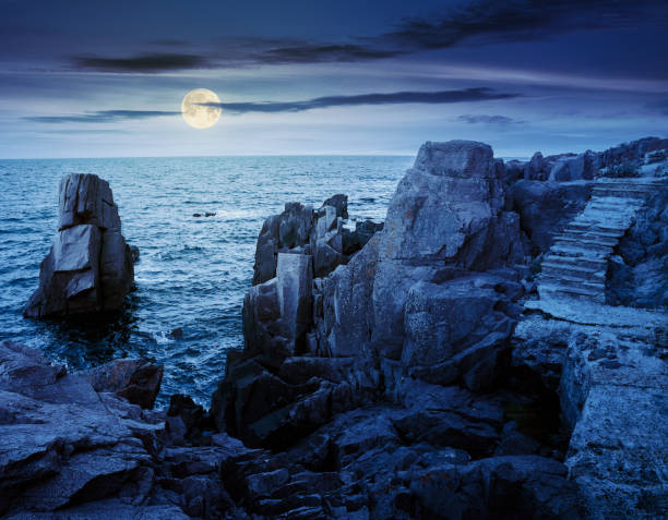 stone steps on rocky cliffs above the sea at night stock photo
