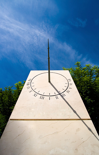 Stone Sundial against a blue sky and some green tree tops.